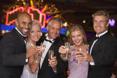 Group of friends celebrating win at casino — Stock Photo