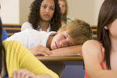 Male college student sleeping through a university lecture — Stock Photo