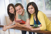 Three college students leaning on banister — Stock Photo