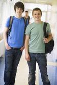 Universitários masculino em pé no corredor da universidade — Foto Stock
