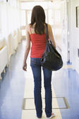 Rear view of female college student in university corridor — Stock Photo