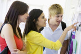 College students looking at a bulletin board — Stock Photo