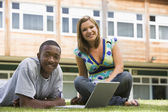 Two college students using laptop on campus lawn, — Foto Stock