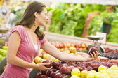 Woman shopping in produce department — Stock Photo