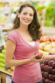 Young woman shopping in produce department — Stock Photo