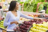 Young woman shopping in produce section — Stock Photo