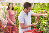 Couple flirting in supermarket aisle — Stock Photo