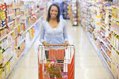 Woman pushing trolley in supermarket — Stock Photo