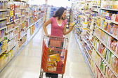 Woman shopping in supermarket aisle — Stock Photo