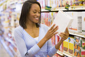 Woman checking food labelling in supermarket — Stock Photo