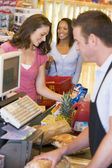 Woman paying for groceries — Stockfoto