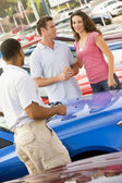 Couple discussing new car with salesman — Stock Photo