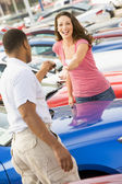 Woman picking up keys to new car — Stok fotoğraf