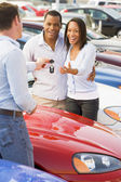 Couple picking up new car from salesman — Stock Photo