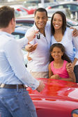 Young family picking up new car — Stockfoto