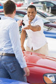 Man collecting new car from salesman — Stock Photo