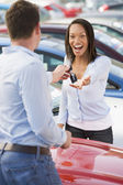 Woman collecting keys to new car — Stockfoto