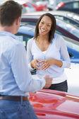 Young woman talking to car salesman — Stock Photo