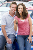 Young couple collecting new car — Stockfoto