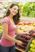Woman choosing apples at produce counter — Stock Photo