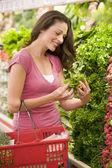 Ung kvinna shopping för råvaror — Stockfoto