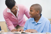 Teacher helping elementary school pupil — Stock Photo