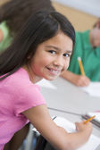 Female pupil in elementary school classroom — Stock Photo