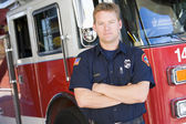 Portrait of a firefighter by a fire engine — Foto Stock