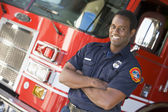 Portrait of a firefighter by a fire engine — Stock Photo