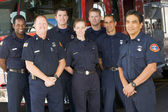 Portrait of firefighters standing by a fire engine — Stockfoto