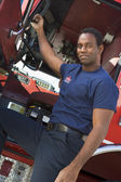 A firefighter standing by the cab of a fire engine — ストック写真