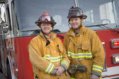 Portrait of two firefighters by a fire engine — Stock Photo