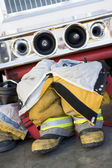 Empty firefighter's boots and uniform next to fire engine — Stock Photo