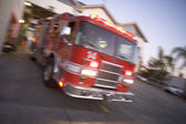 Fire engine rushing out of a fire station — Stock Photo
