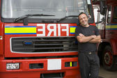 Portrait of a firefighter standing by a fire engine — Stock Photo