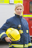 Portrait of a firefighter standing in front of a fire engine — Stock Photo