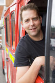 Male firefighter sitting in the cab of a fire engine — Stockfoto