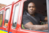 Male firefighter sitting in the cab of a fire engine — Stock Photo