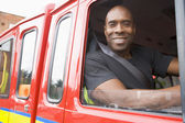 Male firefighter sitting in the cab of a fire engine — Stok fotoğraf