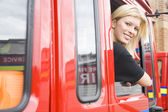 Female firefighter sitting in the cab of a fire engine — Stockfoto