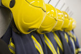 Firefighter's coats and helmets hanging up in a fire station — Stock Photo