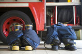 Firefighter's boots and trousers in a fire station — Stok fotoğraf