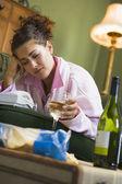 Una mujer joven en su pijama bebiendo vino y viendo la tele — Foto de Stock