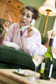A young woman in her pyjamas on the phone and smoking — Stock Photo