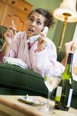 Una mujer joven en su pijama en el teléfono y fumar — Foto de Stock