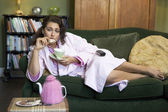A young woman lying on her couch drinking tea — Stock Photo