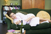 A young woman lying on her couch drinking wine — Stock Photo