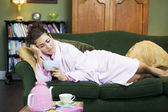 A young woman lying on her couch eating cereal — Stock Photo
