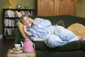 A young woman lying on her couch talking on the phone — Stock Photo