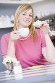 Een jonge vrouw zitten in een cafe het drinken van thee — Stockfoto